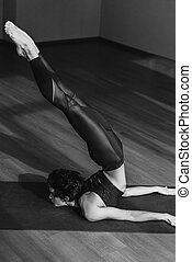 Locust pose - black and white shot of sportive woman in...