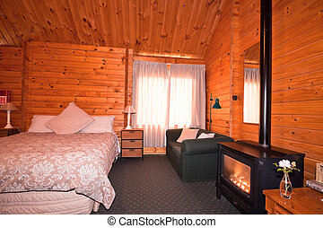Lodge bedroom interior with fireplace. Fox Glacier Lodge, ...
