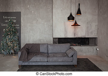 Loft interior with grey concrete walls, fireplace, black chandeliers, velor sofa and decorated christmas tree. Minimalism concept room.