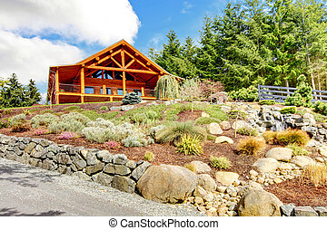 Log cabin home on the hill with waterfall and flowers. -...