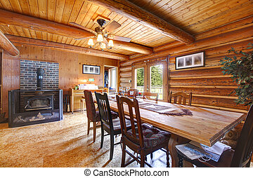Log cabin ruustic living room with large table and stove.