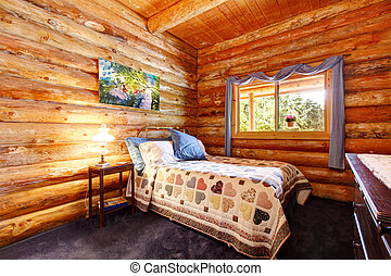 Log cabin rustic bedroom with blue curtains.