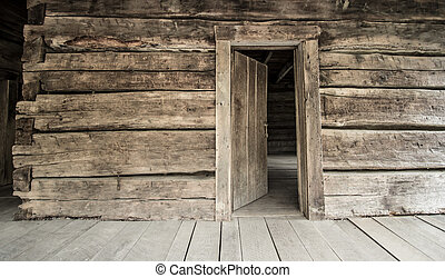 Front porch of Appalachian log cabin with open front door. This is a historical display in the Smoky Mountains National Park and is not a privately owned residence.