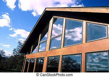 Log Home - Photo of an A frame log home with sky reflecting...