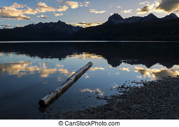 Log in lake at sunset. - A log lays in the shallow water of...