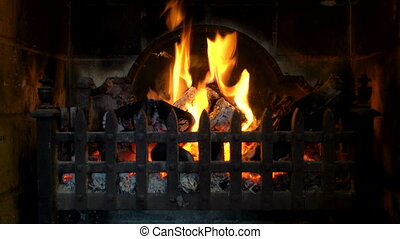 Logs burning in a traditional fireplace.