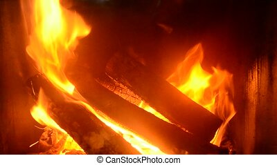 Logs burning in an iron-cast fireplace - Fire with wooden...