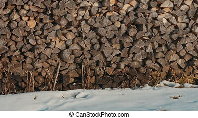 Logs of firewood neatly stacked in the woodpile in winter