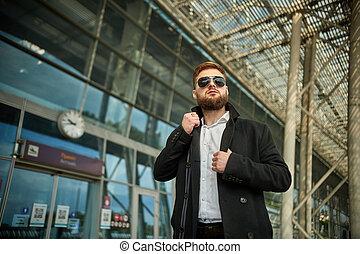 loin, type, homme, regarder, mains, ajustement, lunettes soleil, rouge-tête, collier, deux