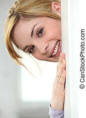loiro, mulher, peeking, atrás de, parede