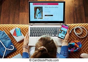 loja, mulher, laptop, enquanto, smartphone, online, roupas comprando