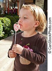 Lollypop - Cute little European toddler girl having fun...