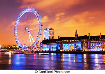 London, England the UK skyline in the evening. Ilumination of the London Eye and the buildings next to River Thames