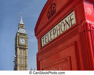 Traditional red telephone box in London with Big Ben in background.