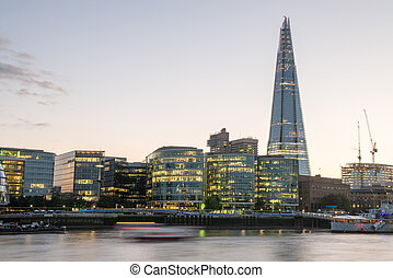 London Skyline at Dusk with City Hall and Modern Buildings, River Thames on foreground - UK