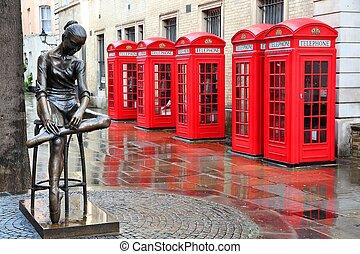 London, United Kingdom - red telephone boxes in wet rainy...