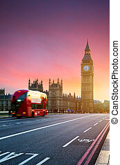 London, the UK. Red bus in motion and Big Ben, the Palace of Westminster. The icons of England