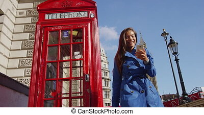 London woman walking by red telephone booth. Big Ben and Westminster Bridge are in the background. Casual professional or female tourist wearing blue trench coat by phone booth. RED EPIC SLOW MOTION.