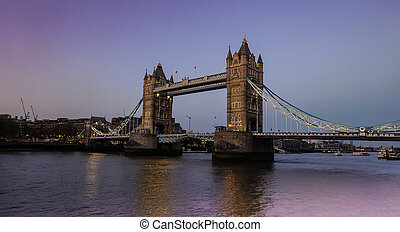 City views along the famous Tower Bridge in the evening with blue skies and reflections in Thames River.