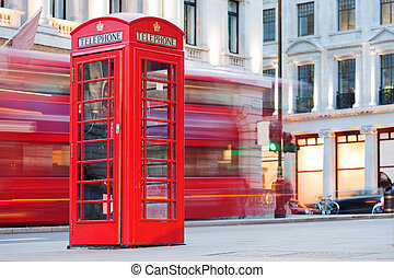 London, UK. Red telephone booth and red bus passing. Symbols...