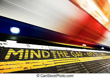 London underground. Mind the gap sign, train in motion.