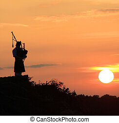 Lone bagpiper at dusk playing his music.