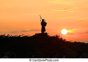 Lone bagpiper at sunset - Lone bagpiper plays his song at...