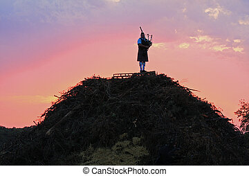Lone bagpiper on a hill at dusk, playing a sad song