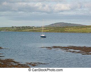 Lone Boat - A lone sailboat on the sea.