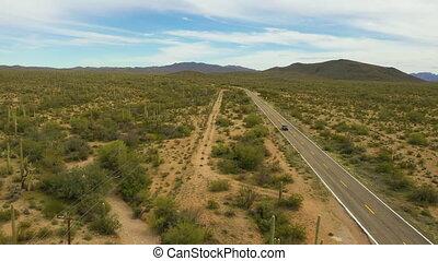 Lone car drives on Highway in Arizona through Sonoran Desert