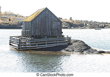 A single fishing shack, alone on the water. Photo taken in Lunenburg, Nova Scotia, Canada