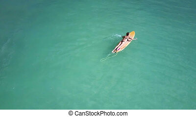 lone girl surfer swims on board and guy appears - lone slim...