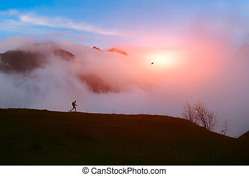 Lone hiker in the mountains at sunset with clouds