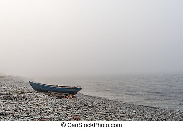 Lone landed rowboat by seaside