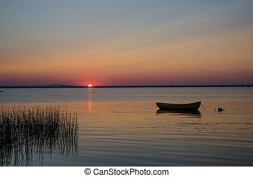 Lone rowboat in calm water at sunset with the Oland Bridge ...