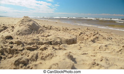 Lone sandcastle fort pyramid closeup on the sunny beach...