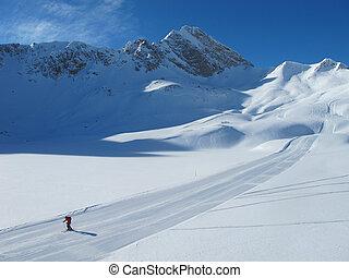 Lone skier on ski piste on sunny winter day