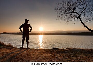 Lone sportsman looking at colorful sunset on shore of autumn lake