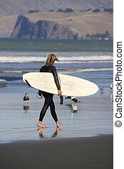 A young woman surfer walks across a beach with her surf board