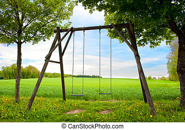 Lone swing seat in a summer field