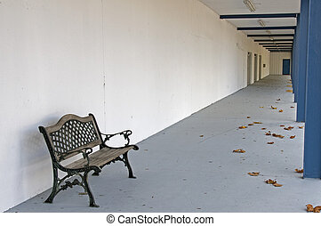 Lone weathered bench remains after store closing during a bad economy