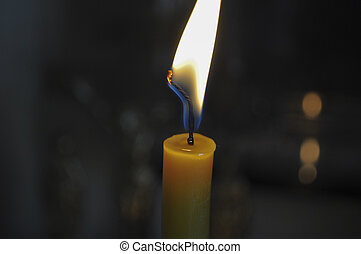 Lone yellow candle - yellow candle burning with a bright...