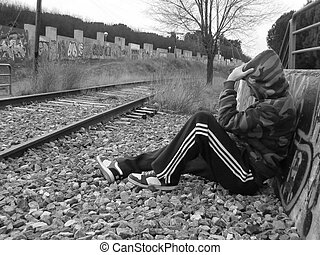 loneliness - lonely boy sitting next to train tracks