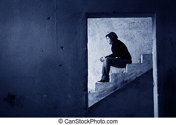 loneliness - lonely girl on the stairs of an abandoned...