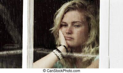 Loneliness - Young girl looking out of a window