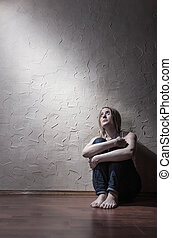 Loneliness - Young sad woman sitting alone on the floor in...