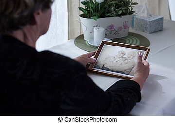 Lonely aged female holding photo - Picture of lonely aged...