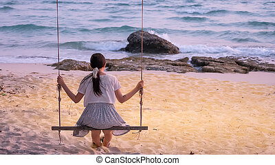 lonely Asian woman sitting on swing at the beach