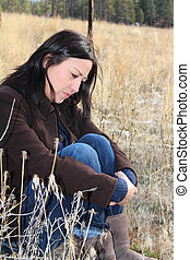 Lonely - Beautiful brunette female sitting in a field