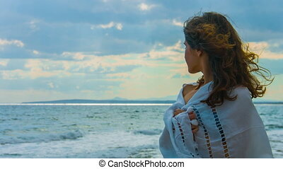 """Lonely beautiful woman covered with scarf standing near sea, looking at storm"""